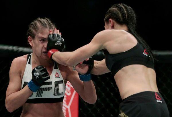 Joanna Jedrzejczyk, right, lands a punch on Karolina