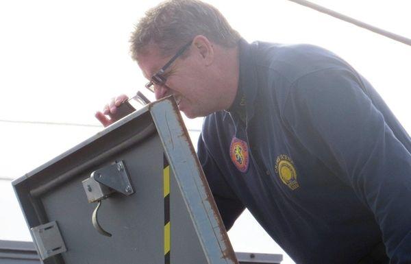 A Nassau police investigator examines a roof hatch
