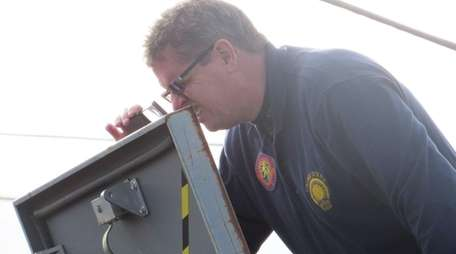 A Nassau police investigator examines a roof hatch