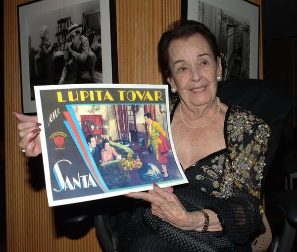 Actress Lupita Tovar holds a poster from one