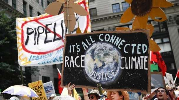 Climate change activists carry signs as they protest