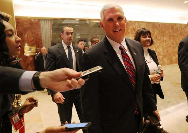 Vice President-elect Mike Pence walks by reporters while