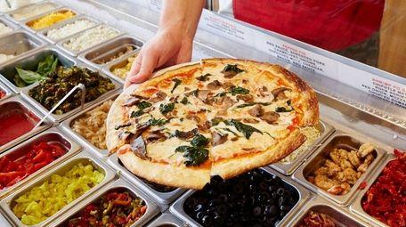 A finished pie with tomato sauce, mozzarella, mushrooms