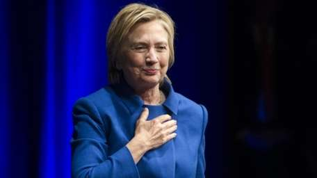 Hillary Clinton places her hand over her hand