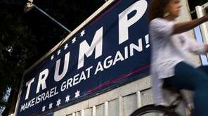 An Israeli cyclist passes a placard proclaiming 'Trump