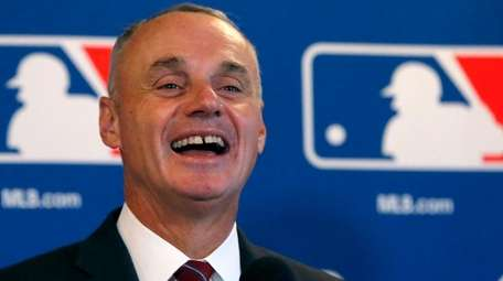 MLB commissioner Rob Manfred laughs as he responds