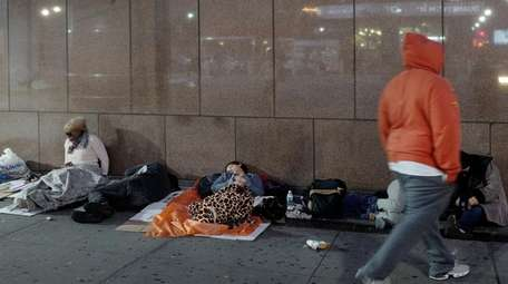 Homeless people sleep under blankets outside Madison Square