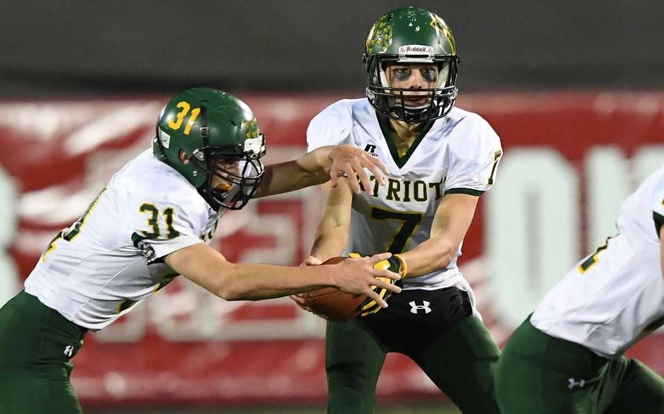 Ward Melville quarterback Wesley Manning hands the ball