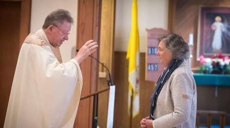 Religious scholar Phyllis Zagano is blessed by Msgr.