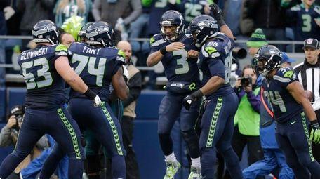 Seattle Seahawks quarterback Russell Wilson (3) is greeted