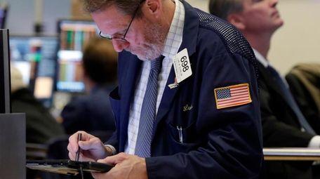 Trader Luke Scanlon, left, works on the floor