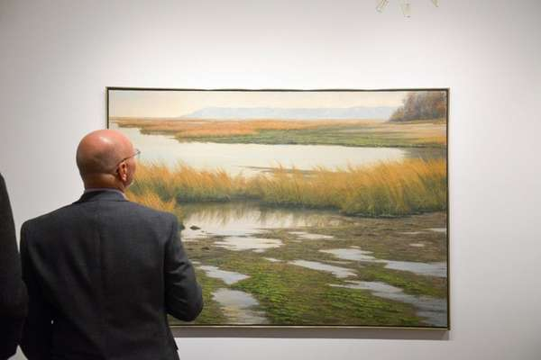 An art enthusiast takes in the detail of
