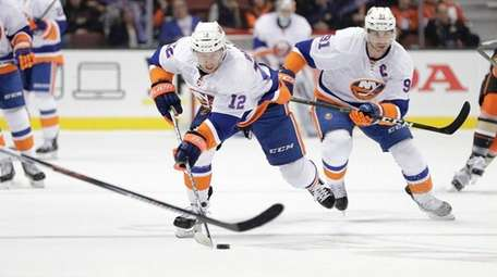 New York Islanders' Josh Bailey, center, moves the