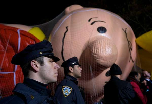 NYPD officers stand stand near parade balloons after