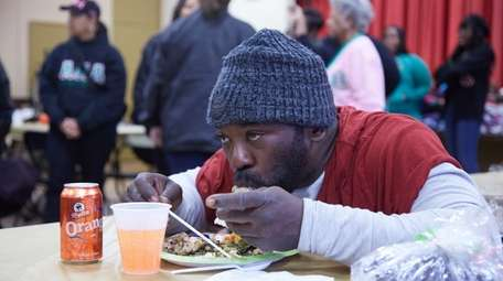 Patrick McGrue, 47, of Roosevelt, eats a free