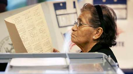 A woman looks over the instructions for voting