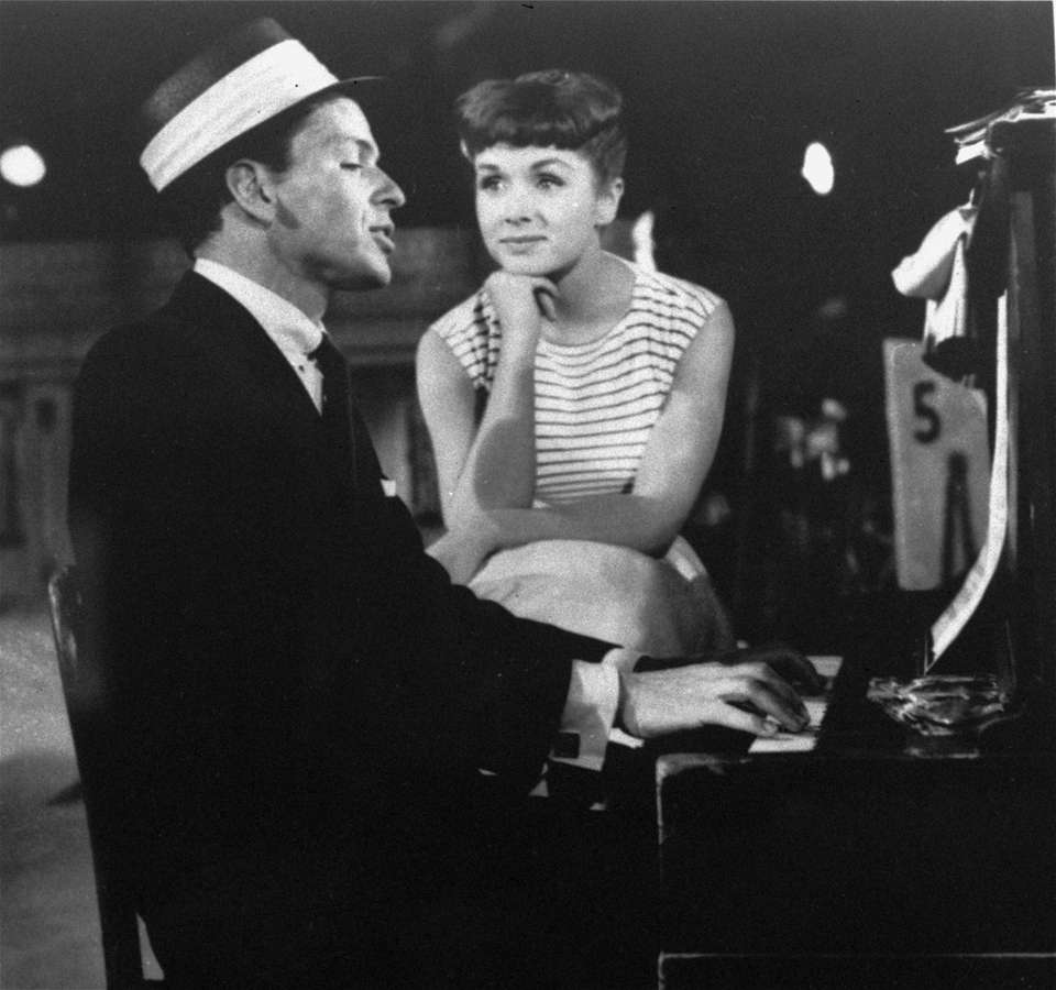 Frank Sinatra sings to Debbie Reynolds during a