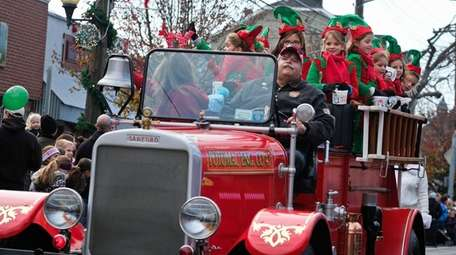Sayville firefighters drive down the street during the