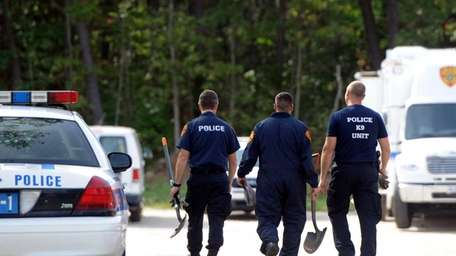 Suffolk County police investigators probe a wooded area