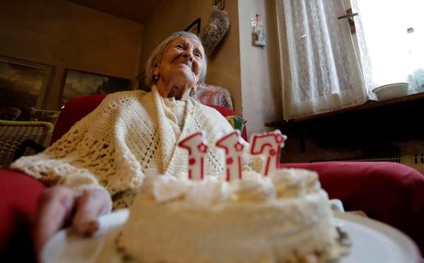 Emma Morano holds a cake with candles marking