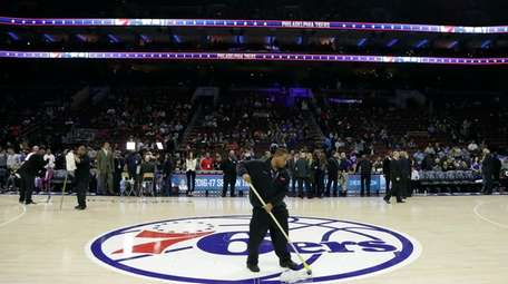 A building worker wipes the court before an