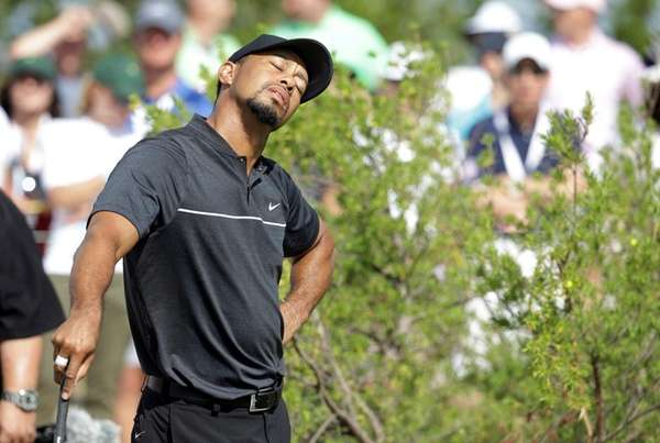 Tiger Woods stretches before teeing off on the