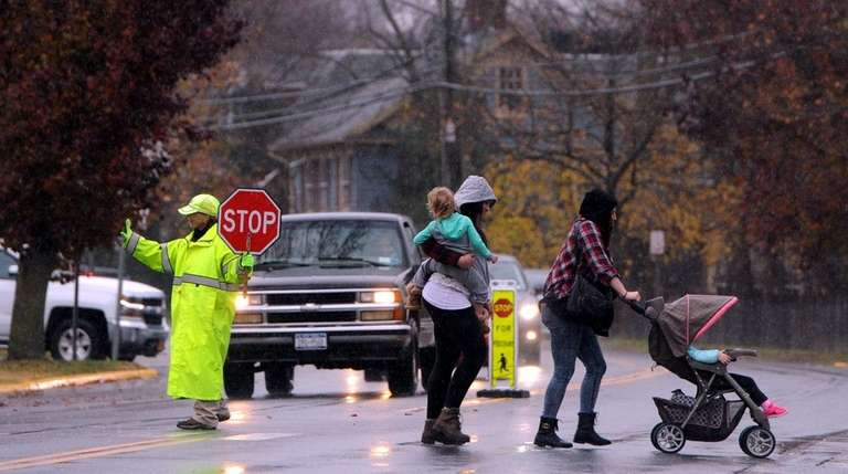 A crossing guard holds traffic on Main Street
