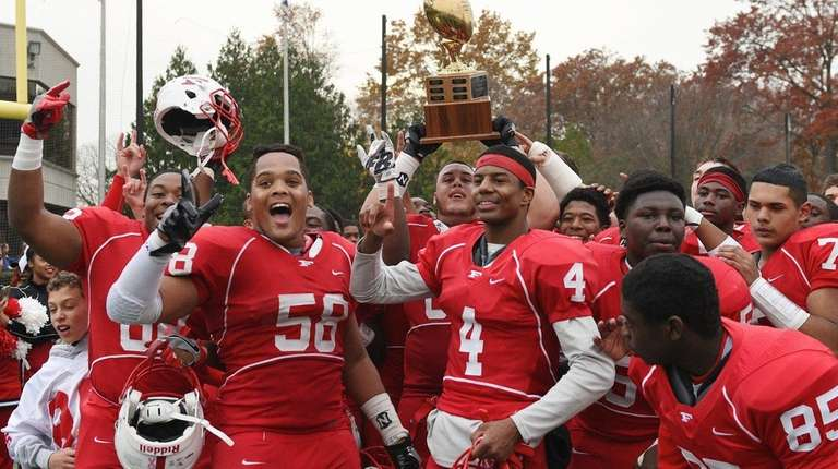 Freeport players raise their championship trophy after defeating