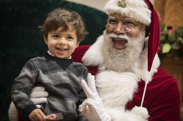 Larry Jefferson, playing the role of Santa, poses