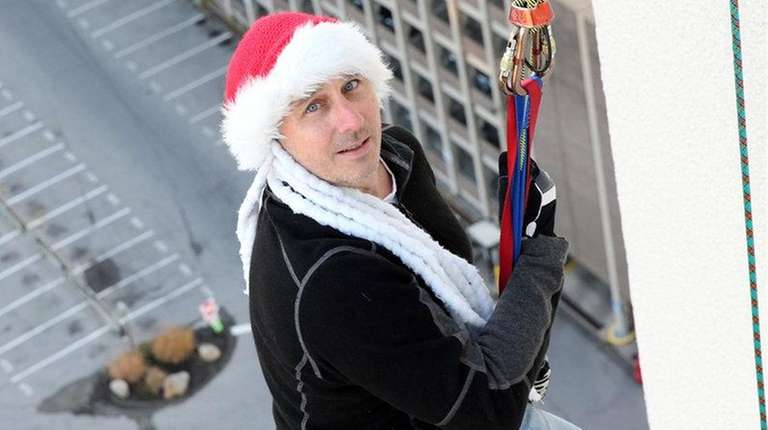 Yankees general manager Brian Cashman rappels from the