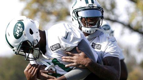 Jets' Brandon Marshall, right, grabs Quincy Enunwa between