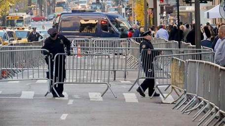 NYPD officers place barriers to create a secure