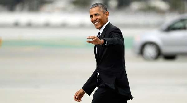 President Barack Obama waves as he walks to