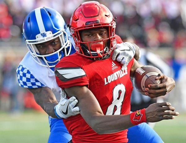 Louisville quarterback Lamar Jackson is dragged down from