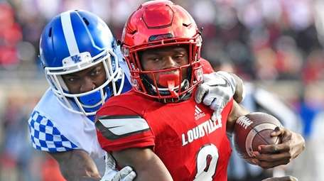 Louisville quarterback Lamar Jackson is dragged down from