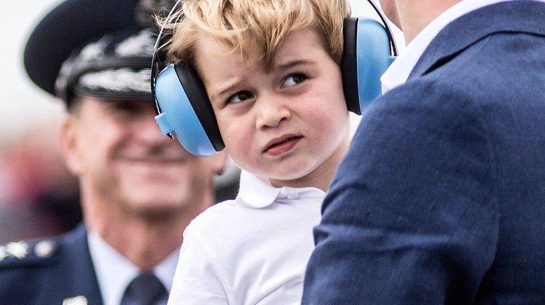 Prince George, wears ear defenders against the roar