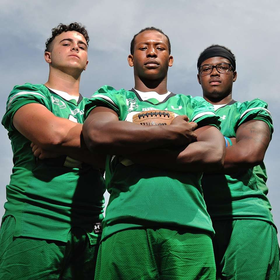Jordan McLune, Farmingdale running back, center, poses for