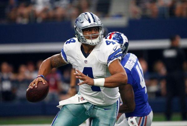 Dallas Cowboys quarterback Dak Prescott scrambles out of