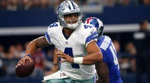Dallas Cowboys quarterback Dak Prescott scrambles out of