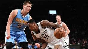 Nets' Rondae Hollis-Jefferson drives the ball against Nuggets'
