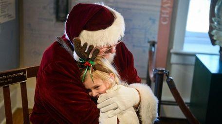Sierra Stachurski, 4, of Amityville, hugs Santa during