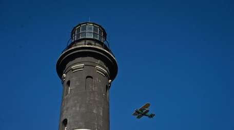 An airplane with presents flies past the lighthouse