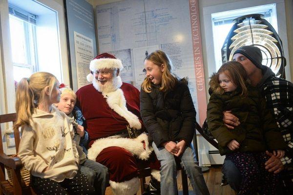Santa greets, from left, Brianna Sipel, 7, of
