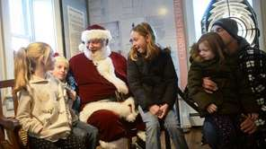 Santa greets, from left, Brianna Sipel, 7, of