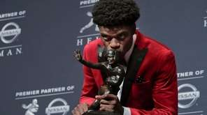 Louisville's Lamar Jackson poses with the Heisman Trophy