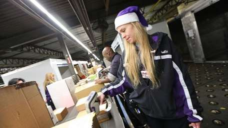 FedEx courier Tami Cunningham processes packages at the