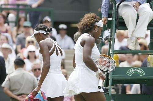 Venus Williams, left, and Serena Williams cross at