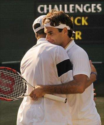 Switzerland's Roger Federer (R) embraces Andy Roddick after