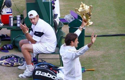 Andy Roddick looks despondent as Roger Federer of