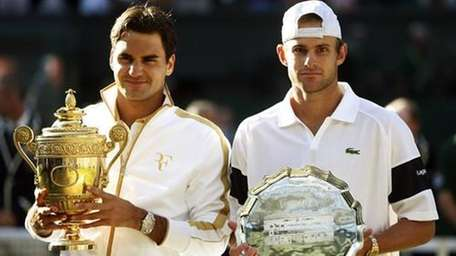 Roger Federer of Switzerland, left, holds his trophy